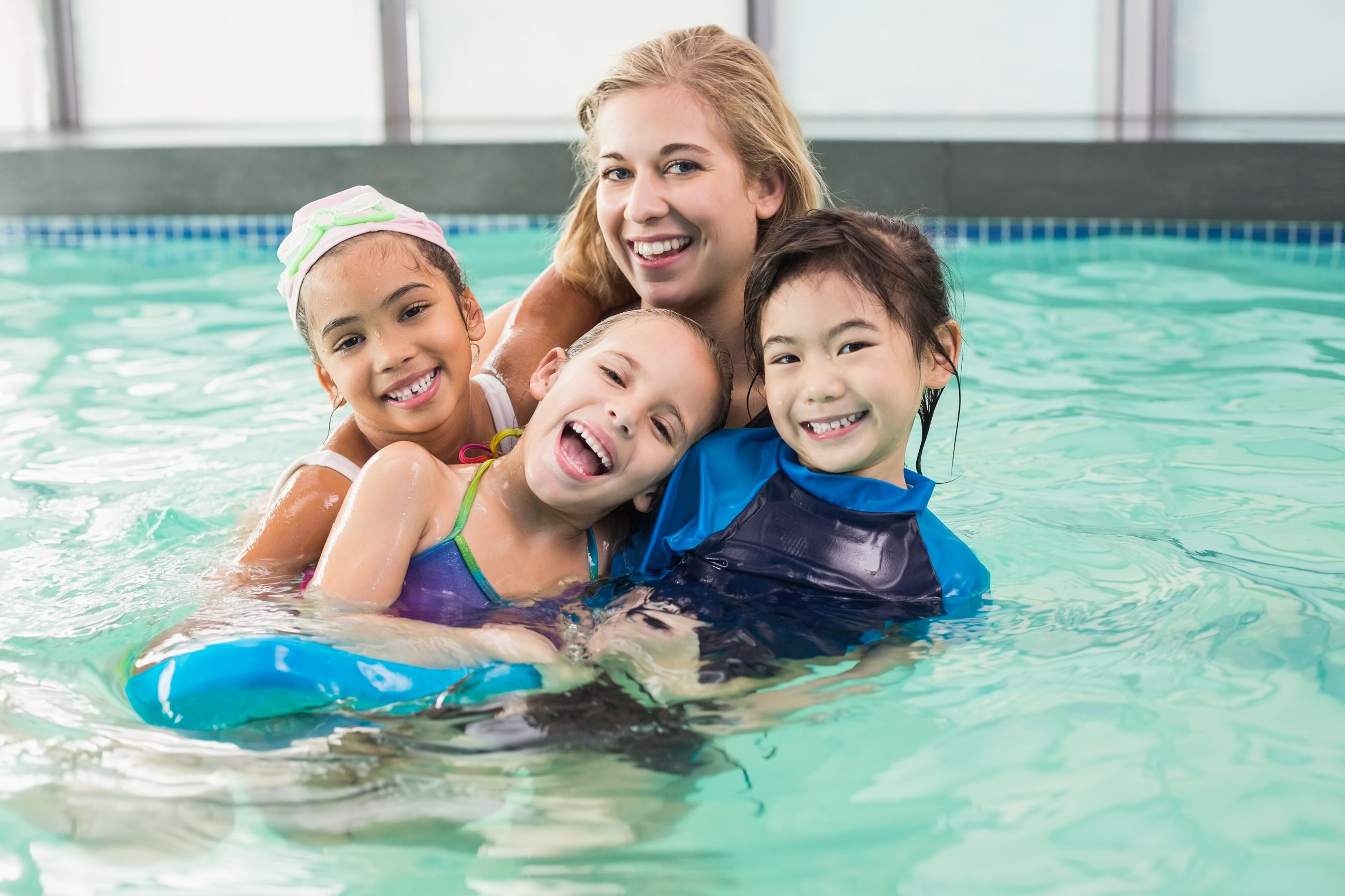 Swimming instructor and kids in pool for swim lessons